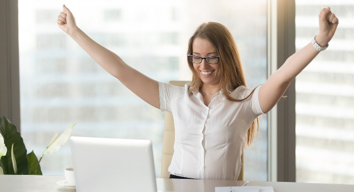A Lady sitting at a desk celebrating success with her arms in the air.
