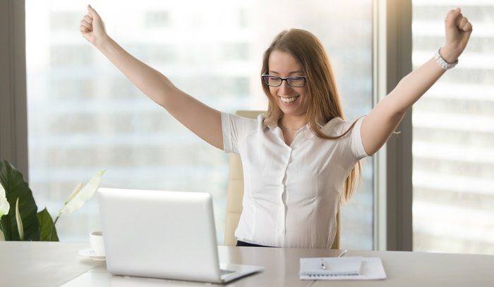 A lady sat at her computer with her arms raised celebrating.