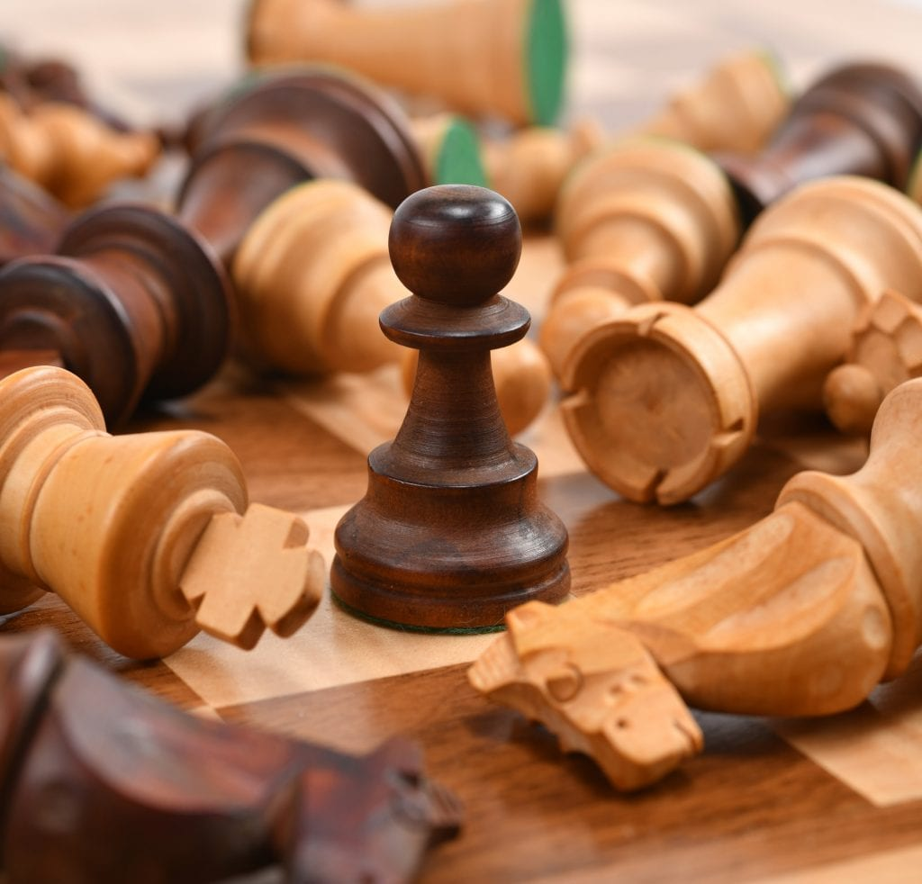 Fallen chess pieces amongst a standing pawn.