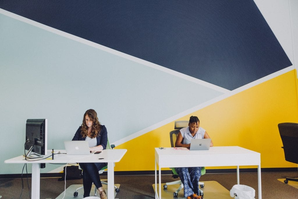 Two women working in an office on spaced out desks