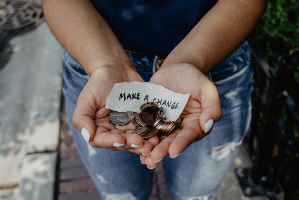 """Someone holding their hands out and holding coins with a piece of paper that says """"make a change"""""""