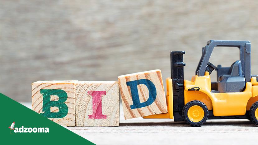 "A yellow forklift pushing three wooden blocks spelling ""BID"""