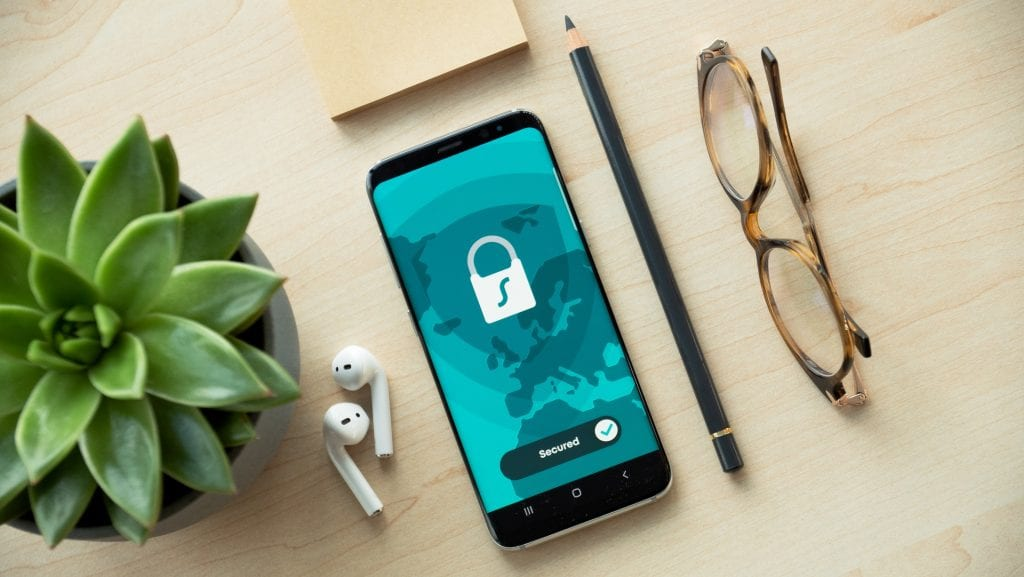 A phone on a desk with a padlock on the screen to signify privacy