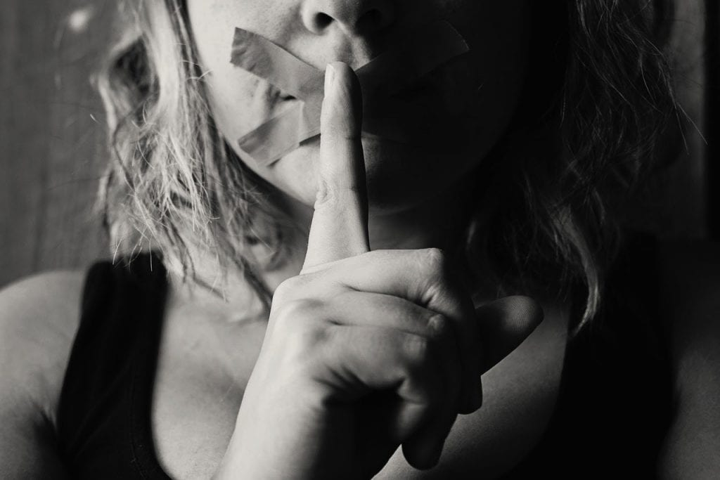 Woman with her finger to her mouth which is also taped shut