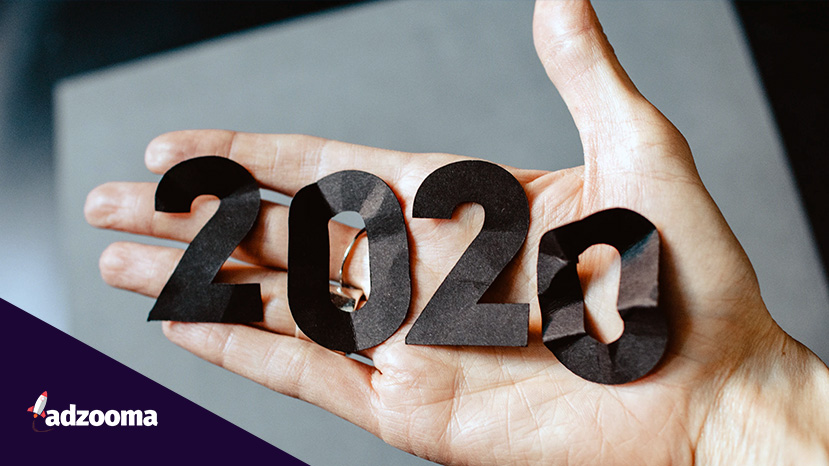 The year 2020 spelt out in cut out paper and held in a hand