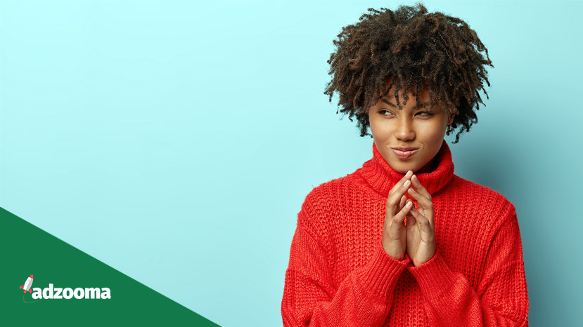 Save Download Preview Pensive black young woman strategist has great plan, holds hands together, looks curiously with intention to do something aside, has great plan, wears red clothes, isolated over blue background